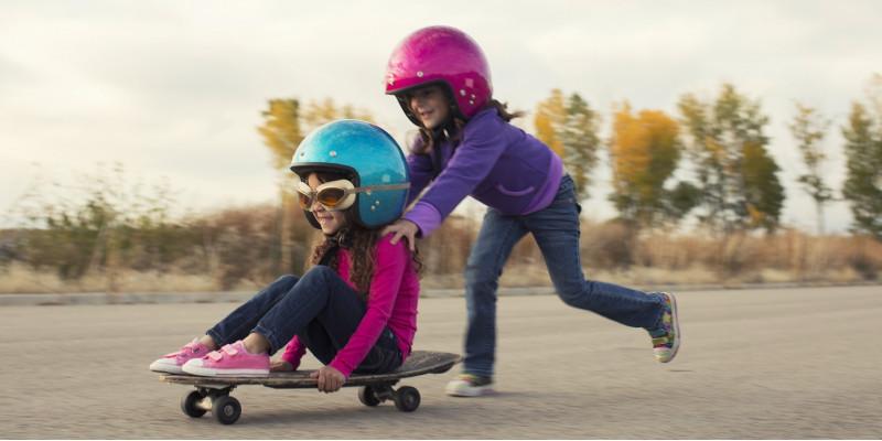 zwei kleine Mädchen mit Sturzhelmen schieben sich gegenseitig auf einem Skateboard auf einem gepflasterten Platz