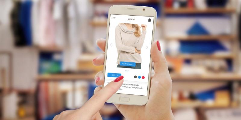 eine Frau bestellt vor ihrem Kleiderschrank mit ihrem Smartphone Kleidung