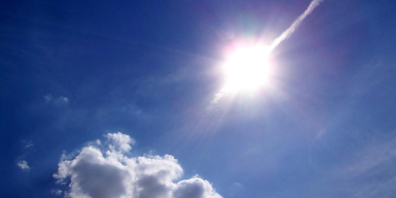 strahlende Sonne an einem blauen Himmel mit Schönwetterwolke