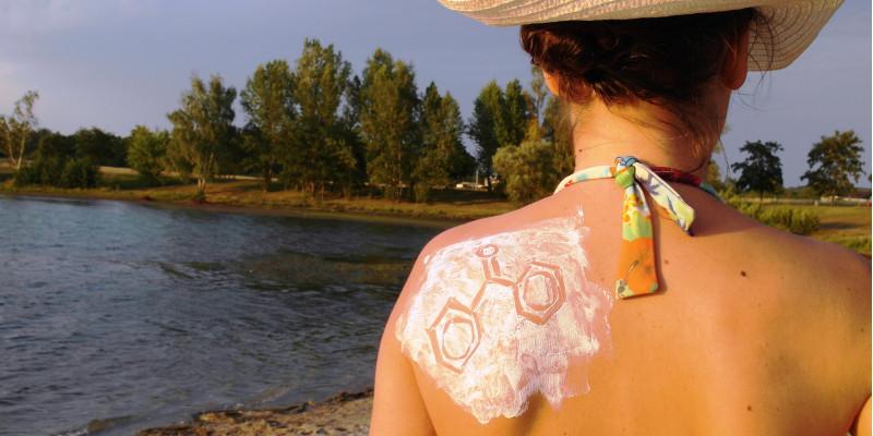 Eine Frau mit Sonnenhut und Bikini steht an einem See. Man sieht Rücken und Hinterkopf. Das linke Schulterblatt ist mit Sonnencreme eingecremt, in die eine chemische Strukturformel gezeichnet ist.