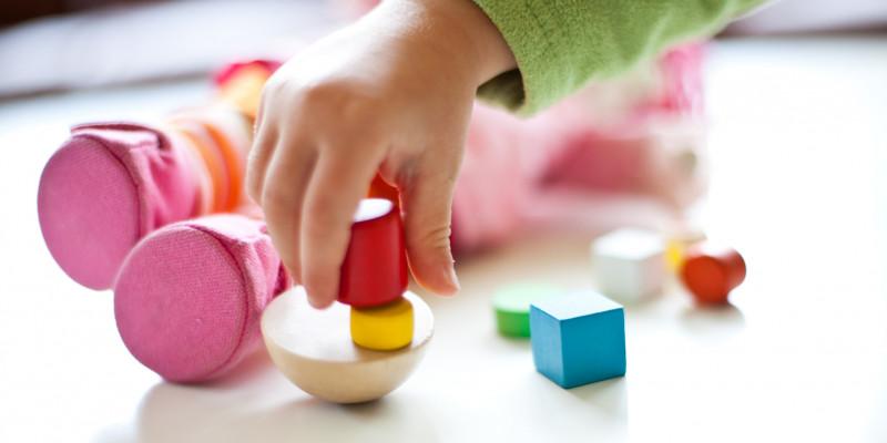 Nahaufnahme einer Kinderhand, die mit Bauklötzen spielt