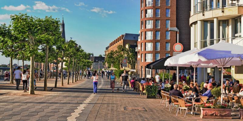 Fußgängerzone in der Stadt, in der Menschen spazierengehen, joggen oder draußen in Cafés sitzen