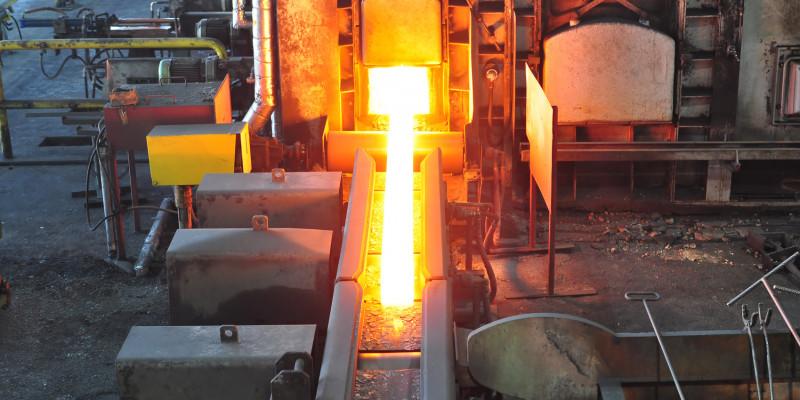 In einem Stahlwerk fließt rotglühender, flüssiger Stahl