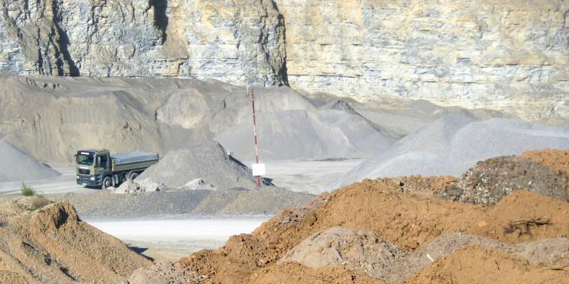 in einem Steinbruch werden Baustoffe abgebaut, man sieht verschiedenfarbige Schüttguthalden und einen Lkw vor einer steilen Felswand