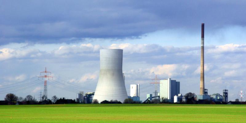 Kraftwerk mit einem Schlot und einem Kühlturm, daneben ist eine Energiefreileitung zu sehen