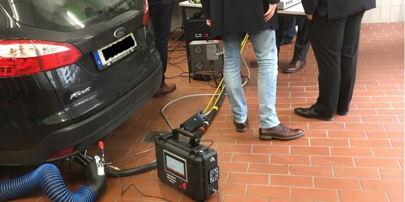 an einem Pkw, der in einem Raum steht, ist ein Messgerät am Auspuff angeschlossen
