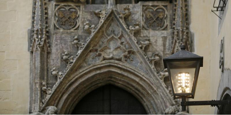 alte Laterne mit Led-Licht vor einem steinernen historischen Eingangsportal