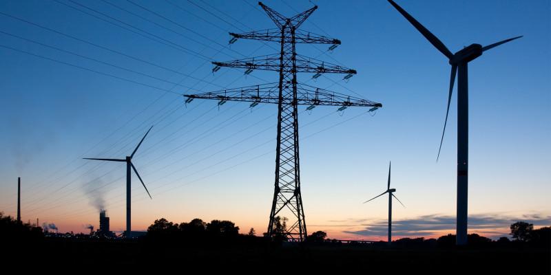 Windkrafträder und Stromtrasse im Dämmerlicht