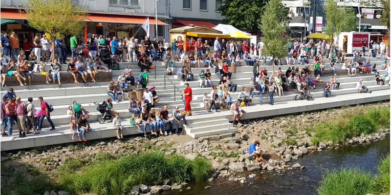 Menschen sitzen auf einer breiten Stufenanlage an einem kleinen Fluss