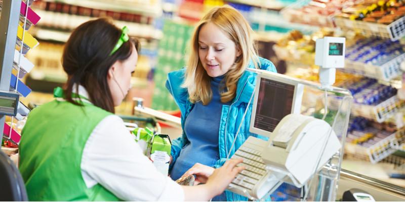 Kundin und Kassiererin an einer Supermarktkasse, die Kassiererin wiegt Gemüse ab, das in einer Plastiktüte verpackt ist