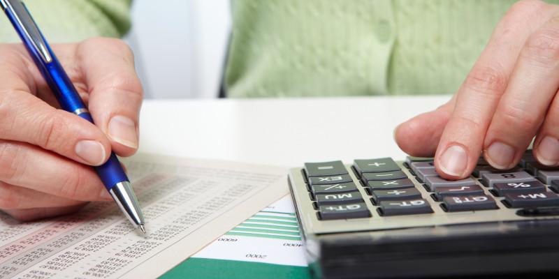 Frau sitzt an einem Schreibtisch und rechnet mit einem Taschenrechner, vor ihr liegt eine Liste mit vielen Zahlen