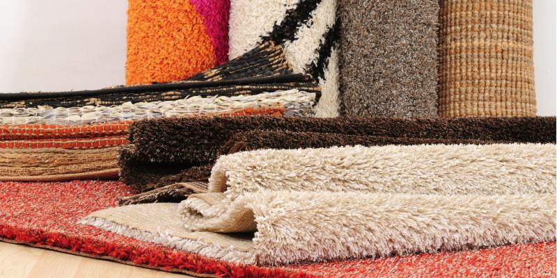 mehrere Teppiche auf einem Haufen, dahinter stehen Teppich-Rollen
