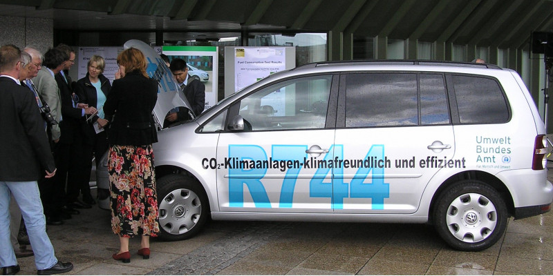 "VW Touran car with the inscription ""CO2-Klimaanlagen - klimafreundlich und effizient, R744"" and the logo of the Umweltbundesamt, beside a group of people"