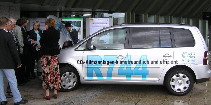 """silbergraues Auto mit der Aufschrift """"CO2-Klimaanlagen - klimafreundlich und effizient, R744"""" und dem Logo des Umweltbundesamtes, daneben eine Gruppe Menschen"""