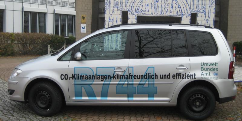 """VW Touran car with the inscription """"CO2-Klimaanlagen - klimafreundlich und effizient, R744"""" and the logo of the Umweltbundesamt"""