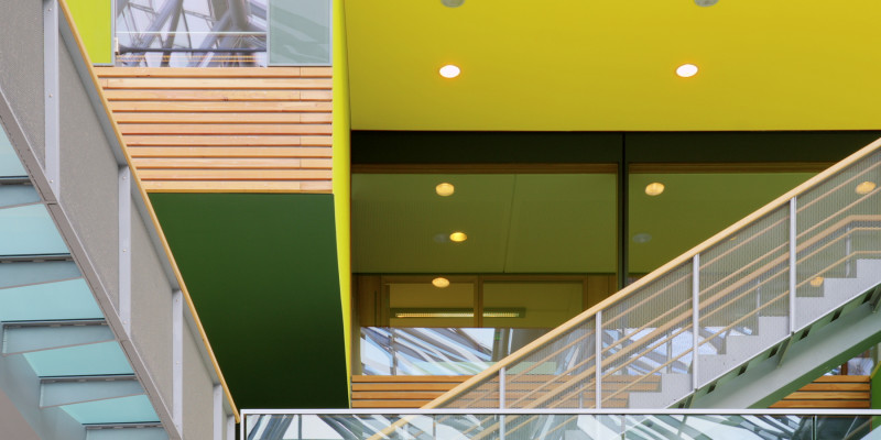 Skywalks and stairs with glass banisters in inner courtyard, inner façade of wood, yellow and green surfaces