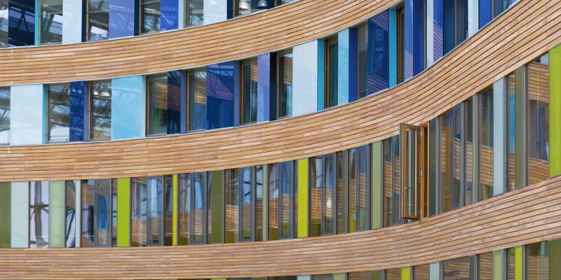 Fassade mit Fenstern, Holzverschalung und bunten Glasplatten in Blau- und Grüntönen