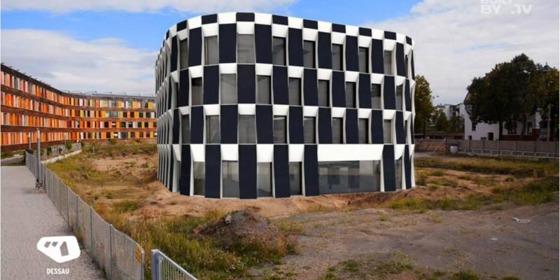 neben dem UBA-Gebäude Dessau-Roßlau ist eine Brache mit Bauzaun. Per Computersimulation wurde der geplante Erweiterungsbau mit seinen großen Photovoltaikelementen an der Fassade, reingesetzt.