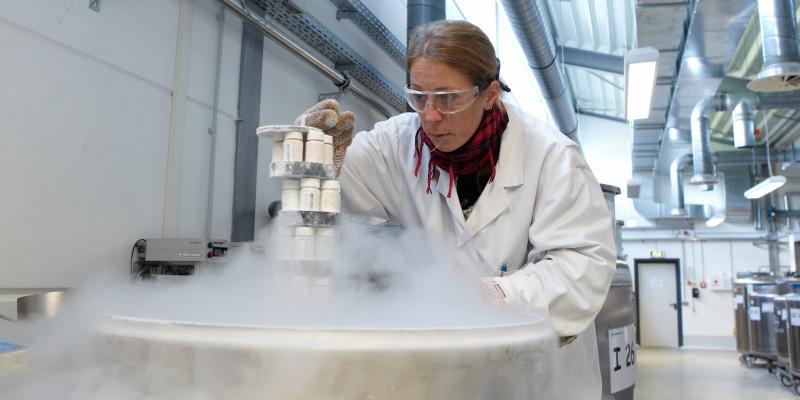 eine Frau in einem weißen Kittel, mit Schal, Handschuhen und Schutzbrille holt Proben aus einem dampfenden Metallbehälter, der in einer Halle steht