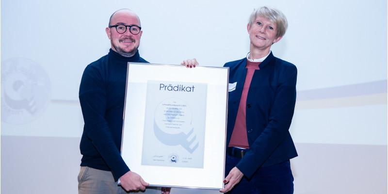 eine Frau und ein Mann posieren mit einer Urkunde für ein Foto