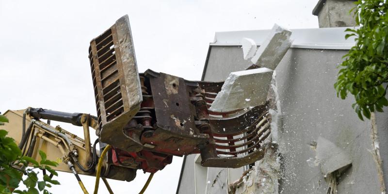 eine Wärmedämmung aus Polystyrol wird von einer Hausfassade abgerissen