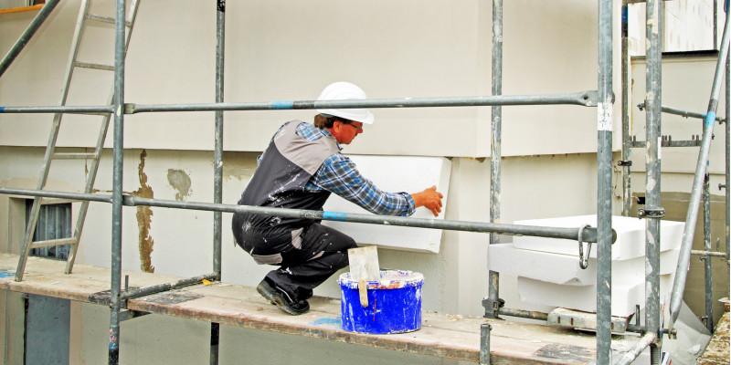 ein Bauarbeiter auf einem Gerüst bringt Dämmplatten aus Polystyrol an einer Hausfassade an