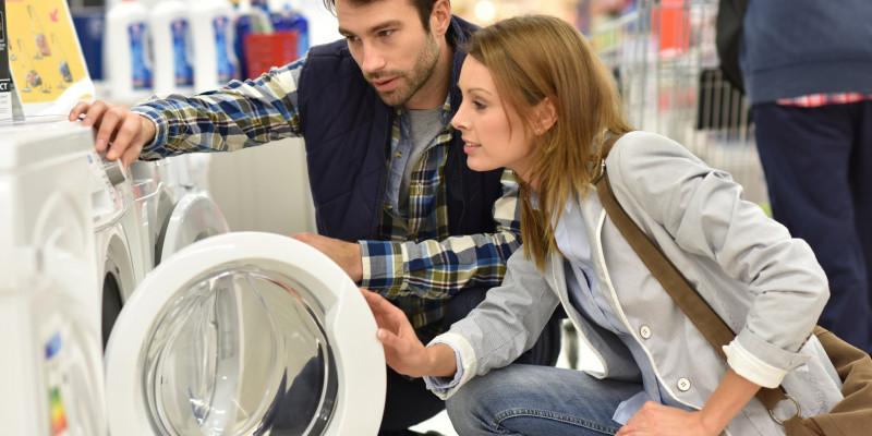 Eine Frau und ein Mann schauen in einem Elektronikmarkt eine Waschmaschine an