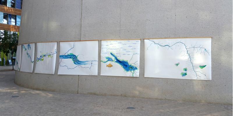 im Vorraum des Umweltbundesamtes Dessau hängen große weiße Bilder nebeneinander, auf denen ein Flusslauf gemalt ist