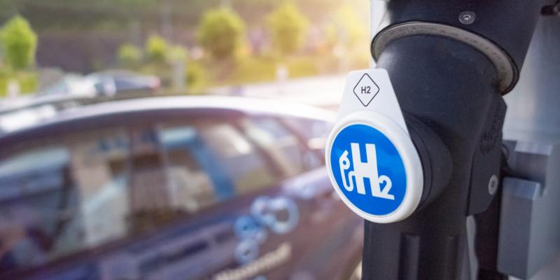 ein Auto steht an einer Tankstelle, auf dem Zapfhahn steht H2