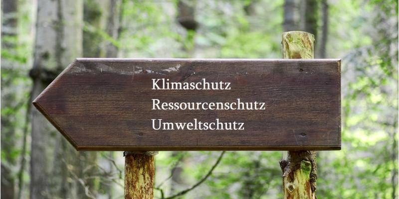 auf einem hölzernen Wegweiser im Wald stehen die Worte Klimaschutz, Ressourcenschutz und Umweltschutz