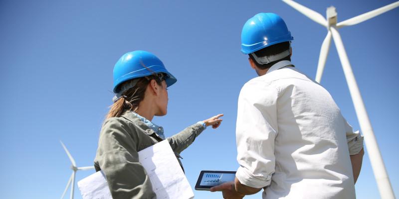 Eine Frau und ein Mann mit Bauhelmen, Plänen und Tablet schauen sich einen Windpark an