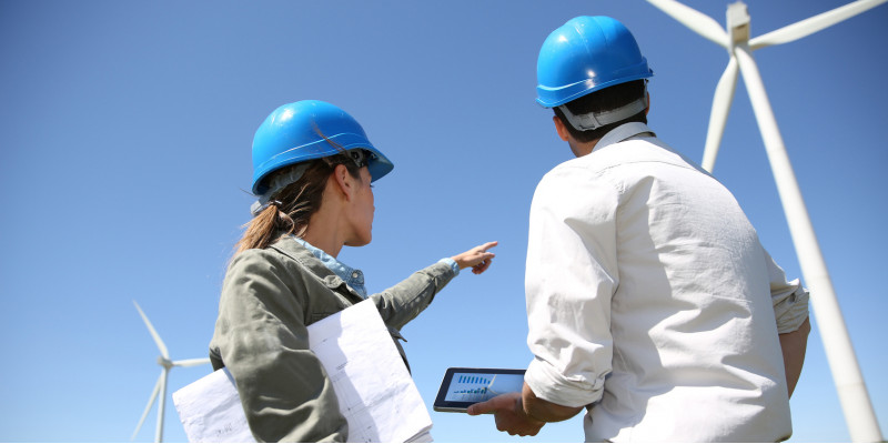 eine Frau und ein Mann mit Bauhelm, Plänen und Tablet schauen sich einen Windpark an