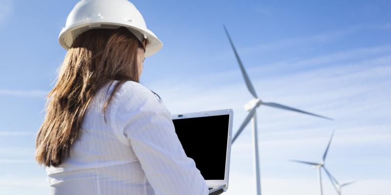 Ingenieurin steht mit Laptop und Bauhelm vor einem Windpark