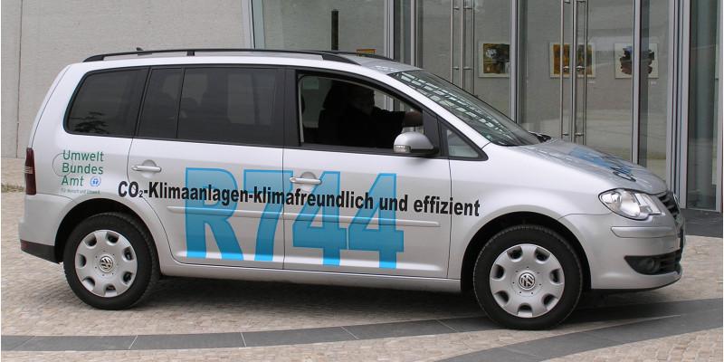 """VW-Auto mit der Aufschrift """"R744, CO2-Klimaanlagen - klimafreundlich und effizient"""" und dem Logo des Umweltbundesamtes"""