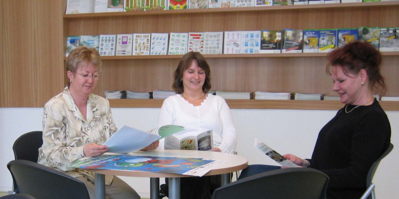 Three women sitting at a round table looking at flyers and brochures, a shelf with more materials in the background