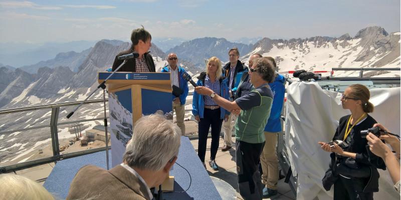 Barbara Hendricks steht auf einer Aussichtsplattform in den Bergen an einem Rednerpult mit Mikrofon, darum versammelt Reporter und andere Personen. Auf den umliegenden Gipfeln liegt Schnee.