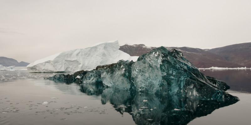 schwarz gefärbter Eisberg im Wasser