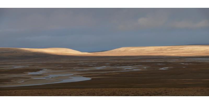 Arktische Landschaft: Die Sonne scheint auf einen Fluss und sanfte braune Hügel.