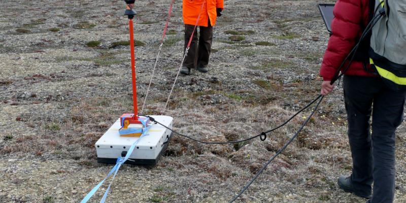 Zwei Forscherinnen stehen mit ihren Instrumenten in der arktischen Landschaft.