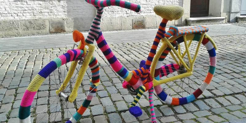 Ein Fahrrad, das komplett mit bunter, gestrickter Wolle umhüllt wurde