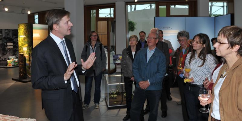 der Kurator erklärt mehreren Besuchern die Ausstellung, im Hintergrund sind einige Exponate zu sehen.