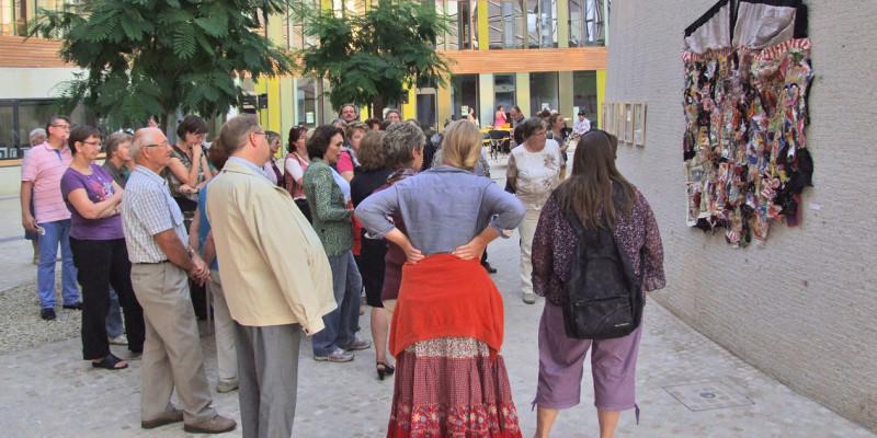 Besucher der Kunstausstellung stehen vor einem geknüpften Wandteppich, der im Atrium des UBA in Dessau hängt