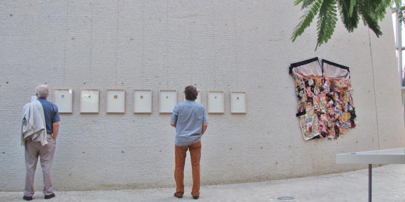 Zwei Männer stehen vor Bilderrahmen mit Textilstücken im Atrium des UBA in Dessau
