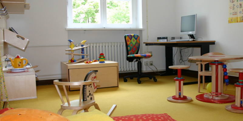 Eltern-Kind-Zimmer: Am Fenster steht ein Schreibtisch umgeben von Spielsachen, einer Spielküche, einer Sitzecke, im Vordergrund eine Matratze mit großem Kissen.
