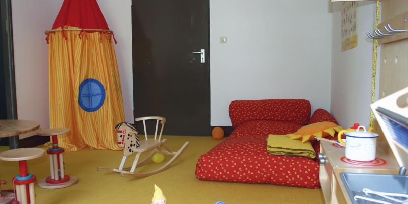 Eltern-Kind-Zimmer: eine Spielecke mit Matratze, Spielküche, Sitzecke und Spielzelt aus Stoff