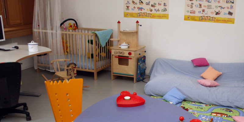 Eltern-Kind-Arbeitszimmer mit einem Schreibtisch, einer Sitzecke und einer Matratze, Spielzeug