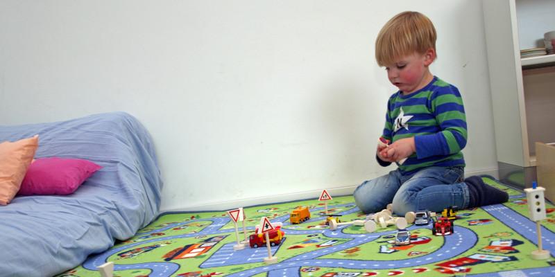 Kind spielt auf einem Teppich, der wie eine Straßenlandschaft aussieht, mit Spielzeugautos.