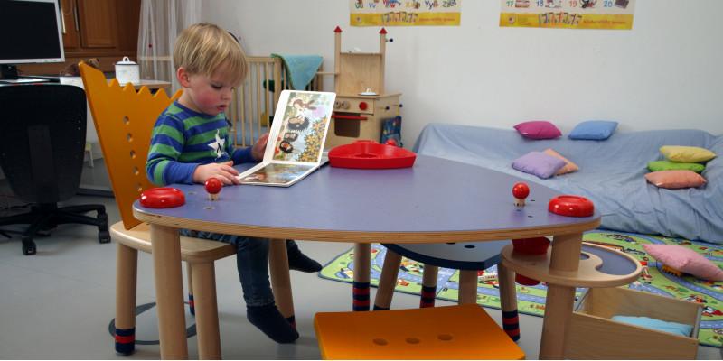Kind sitzt an einem fisch und blättert in einem Bilderbuch.