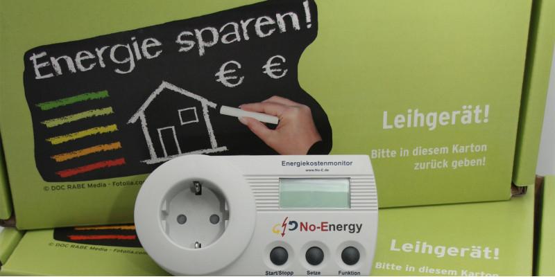 Das Bild zeigt eine hellgrüne Pappkiste mit einem Messgerät für Leerlaufverluste von Elektrogeräten im Vordergrund