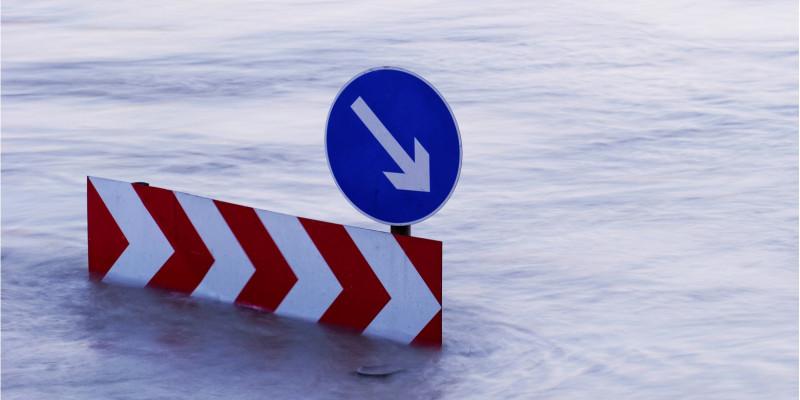 Ein Verkehsschild steht mitten im Hochwasser. Die Straße ist nicht mehr zu sehen.